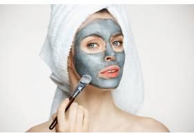 年轻漂亮的女人头上裹着毛巾戴着面具微笑_9028551