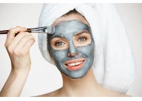年轻漂亮的女人头上裹着毛巾戴着面具微笑_9028556