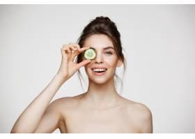 年轻漂亮的裸体女孩微笑着躲在黄瓜片后面_9028208