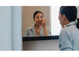 美丽的亚洲女人在镜子前用眉笔化妆快乐的_6141997