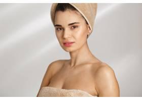 一位美丽时髦的年轻女子沐浴后裹着毛巾站着_8358093