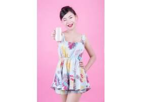 一位美丽的亚洲女子在粉色背景上拿着一瓶产_4524262