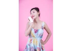 一位美丽的亚洲女子在粉色背景上拿着一瓶产_4524273
