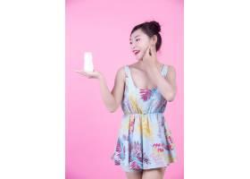 一位美丽的亚洲女子在粉色背景上拿着一瓶产_4524275