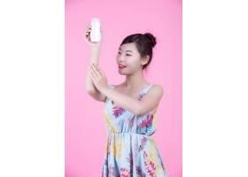 一位美丽的亚洲女子在粉色背景上拿着一瓶产_4524283