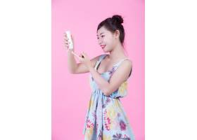一位美丽的亚洲女子在粉色背景上拿着一瓶产_4524288