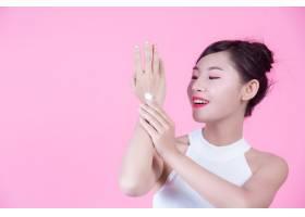 一位美丽的亚洲女子在粉色背景上拿着一瓶产_4525966