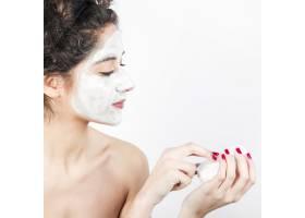 一名妇女在白色背景下在脸上涂抹面膜_3186734