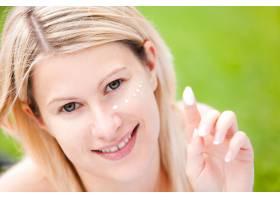 一名妇女在脸上涂抹保湿霜_7064767