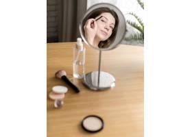 一名妇女在镜子中画眉毛_8368039
