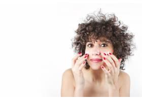 一名年轻女子在白色背景下在脸上涂抹化妆品_3186899