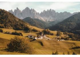 白天美丽的村庄坐落在一座干草丛生的小山_9282493