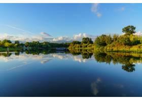 阳光明媚的日子里树木和天空倒映在水面上_10303318