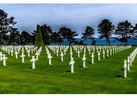 在多云的天空下被绿树环绕的白色石头十字架_12449336
