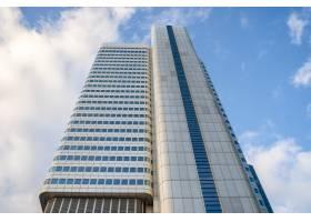 在多云的天空和阳光下有蓝色窗户的高层建筑_10758912
