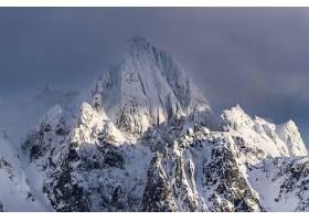 在挪威多云的天空下一座覆盖着白雪的令人_9077131