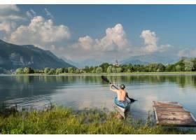 一个人在被树木和山脉包围的湖上划船的美丽_11540884