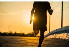 一位年轻的健身者在日出时跑步的剪影_5212277