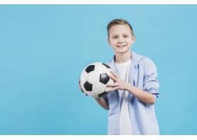 一位微笑的男孩手持足球站在蓝天的映衬下_4165906