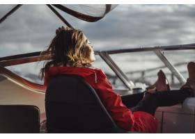 一位身穿红色雨衣的漂亮年轻女子乘坐一艘私_3737917