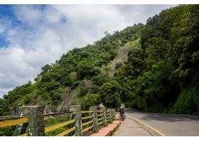 一只猴子坐在高速公路边背景是一座高山_1278037