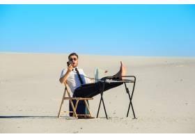 一名商人在沙漠中使用笔记本电脑_8679245