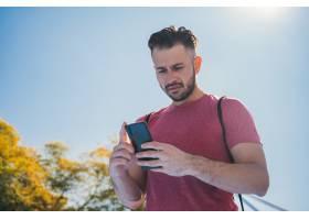 一名年轻男子在训练前查看手机的低角镜头_12908911