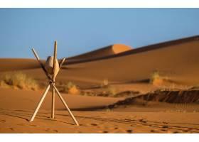用特写镜头将岩石放在带有模糊沙丘的棍状三_7926269
