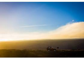 白天一辆越野车在背景为蓝天的小山上的美_9283566