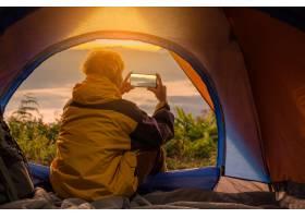 一个年轻人坐在帐篷里用手机拍照_4351619