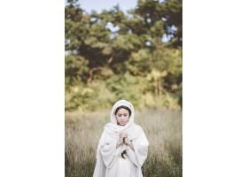 一个穿着圣经长袍闭着眼睛祈祷的女人_9282708
