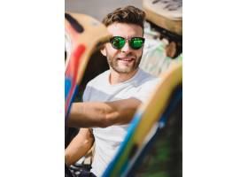 戴墨镜的年轻人坐在一辆敞篷车里_3443846