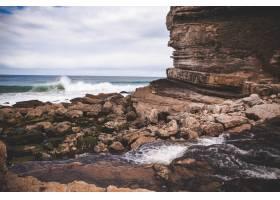 在悬崖附近的海岸上美丽的景色如泡沫般波_13235569