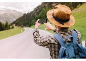 戴着棕色帽子的男性旅行者站在美丽的山上_10561758