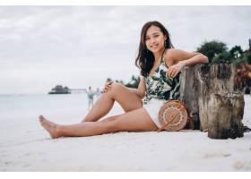 一名亚洲妇女坐在印度洋边的白色沙滩上_5177636