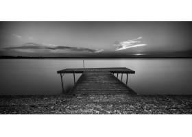 在晴朗的天空下拍摄的海上木制小路的灰度照_9990896