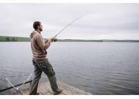 一名男子站在码头上在湖里钓鱼_2698300