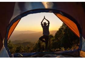 一名男子站在露营帐篷前的瑜伽姿势在早晨的_4351592