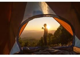 拿着咖啡杯的快乐男子住在山上的帐篷附近_4351590