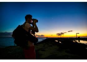 摄影师站在岸上拿着相机身后是美丽的夜空_1275095