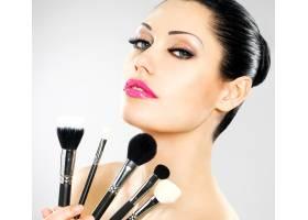 脸上贴着化妆刷的美女漂亮女孩用化妆工具_11994425