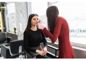 身着黑衣的美女模特在专门的沙龙做化妆程序_9187482