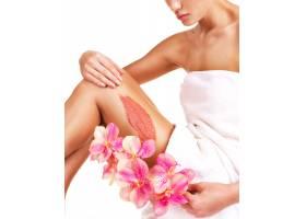 这位身材美丽带着鲜花的女子在她的腿上穿_12115043