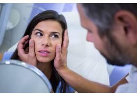医生在整容治疗后检查患者的皮肤_8896262
