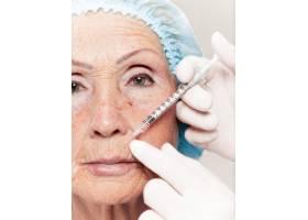 外科医生在整形手术前对中年女性进行皮肤检_7308081