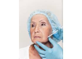 外科医生在整形手术前对中年女性进行皮肤检_7308088
