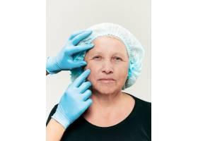 外科医生在整形手术前对中年女性进行皮肤检_7308096