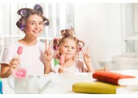 小女孩和妈妈坐在一起吃冰激凌_11648874