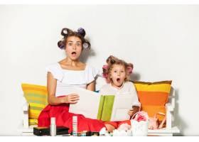 小女孩和妈妈坐在一起看着相册_8609578