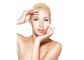 年轻女子在干净清新的脸上涂抹化妆品_12264186